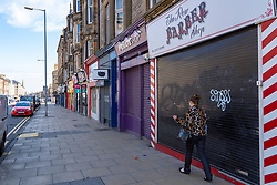 Edinburgh, Scotland, UK. 1 May 2020. Views of Edinburgh as coronavirus lockdown continues in Scotland. Streets remain deserted and shops and restaurants closed and many boarded up. Pictured; Closed shops and few people on Leith Walk.   Iain Masterton/Alamy Live News