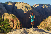 Krissy Moehl topping out near the west rim with angels landing and the zion canyon far below her. Zion National Park, Utah