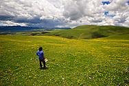 A Tibetan Cowboy waits for a friend on a remote mountain near Litang, Tibet (China).