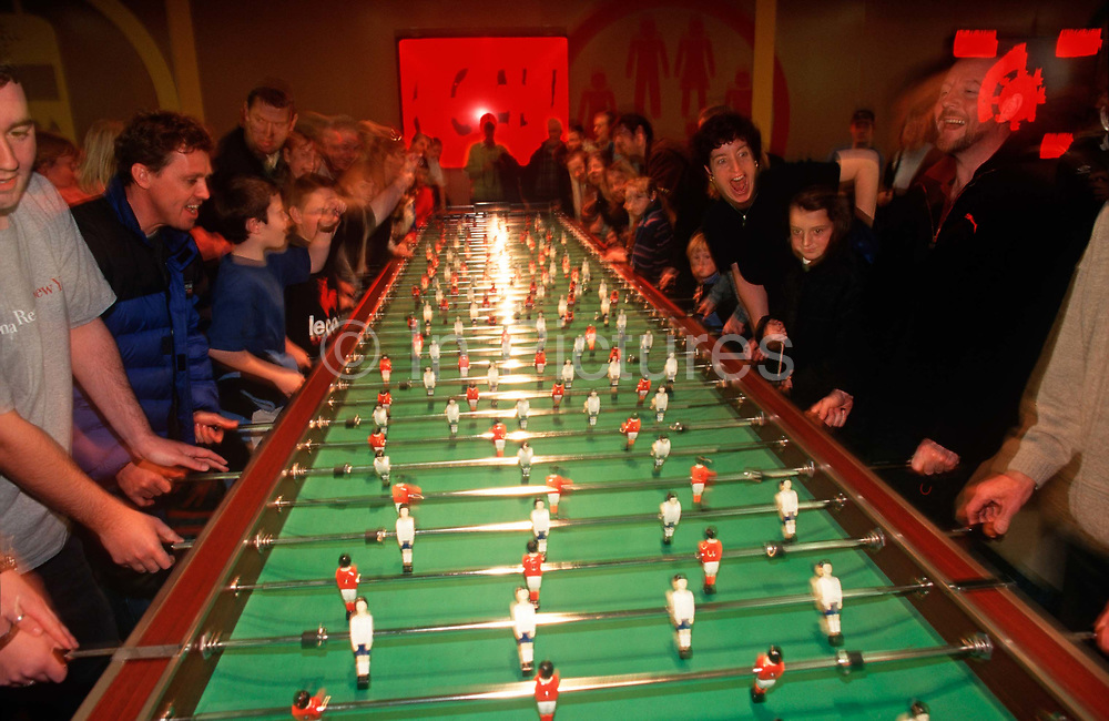 Visitors enjoy a game of giant fussball table inside The Millennium Dome later to become the 02 Arena weeks after the Millennium, on 14th January 2000, in London, England.