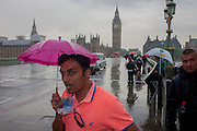 A wet tourists covers his head with a child's silly pink umbrella while visiting London's Southbank, enduring heavy summer rainfall on Westminster Bridge, England.