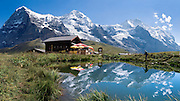 "The peaks of Eiger, Mönch, and Jungfrau (Ogre, Monk, and Virgin) reflect in a pond at Kleine Scheidegg in the Berner Oberland, Switzerland, the Alps, Europe. The world's longest continuous rack and pinion railway (Wengernalpbahn) goes from Grindelwald up to Kleine Scheidegg and down to Wengen and Lauterbrunnen. From Kleine Scheidegg, another cog train (Jungfraubahn) ascends steeply inside the Eiger to Jungfraujoch, the highest railway station in Europe. UNESCO lists ""Swiss Alps Jungfrau-Aletsch"" as a World Heritage Area (2001, 2007). Panorama stitched from six images. Published in September/October 2007 Sierra Magazine, Sierra Club Outings. Published in ""Light Travel: Photography on the Go"" book by Tom Dempsey 2009, 2010."