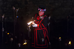 "© Licensed to London News Pictures. 05/11/2018. LONDON, UK. A Yeoman Warder ceremonially lights the first flame followed by volunteers proceeding to light the rest of the installation, gradually creating a circle of light, radiating from the Tower.  A new installation by designer Tom Piper called ""Beyond the Deepening Shadow: The Tower Remembers"", is now open for the public to view at the Tower of London until Armistice Day 2018.  The moat is filled with thousands of individual flames commemorating the centenary of the end of the First World War.   Photo credit: Stephen Chung/LNP"