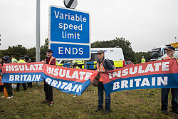 Insulate Britain climate activists hold banners after a M25 slip road at Junction 14 close to Heathrow airport was blocked as part of a campaign intended to push the UK government to make significant legislative change to start lowering emissions on 27th September 2021 in Colnbrook, United Kingdom. The activists are demanding that the government immediately promises both to fully fund and ensure the insulation of all social housing in Britain by 2025 and to produce within four months a legally binding national plan to fully fund and ensure the full low-energy and low-carbon whole-house retrofit, with no externalised costs, of all homes in Britain by 2030.
