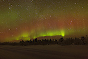 Auroral band over the Finnish forest near Inari, with a bright burst of green in one area.