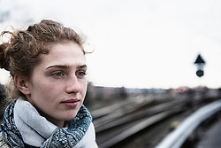 Close-up of young woman thinking with railway tracks in the background, Munich, Bavaria, Germany
