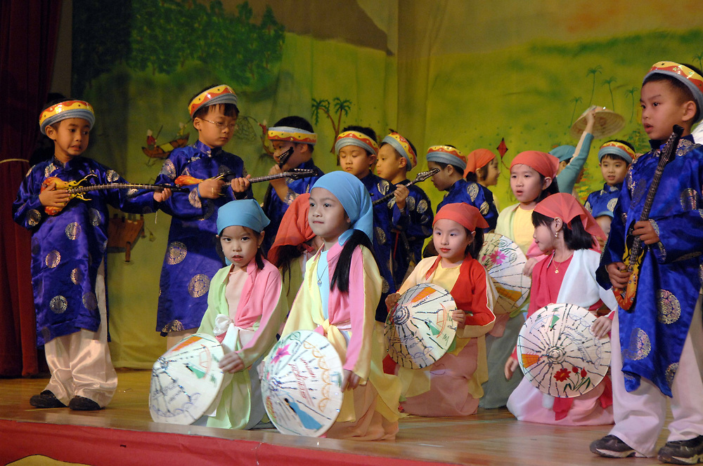 "Austin, TX February 3, 2007: Third Grade (3rd grade) Vietnamese-American boys and girls perform ""Lien Khuc Xuan"" or ""A Spring Medley"" at a Year of the Pig new year's celebration at Walnut Creek Elementary School.  ©Bob Daemmrich /"