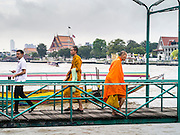 09 OCTOBER 2012 - BANGKOK, THAILAND:  Buddhist monks walk along a pier to and from a ferry on Chao Phraya River. PHOTO BY JACK KURTZ