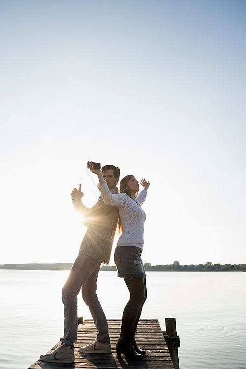 Young happy couple dancing jetty sunset