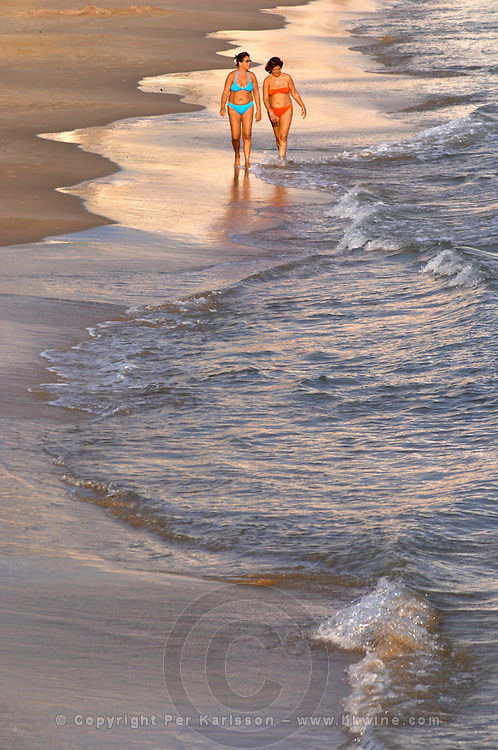 The beach. Two women in bikini. Walking in the water. Sitges, Catalonia, Spain
