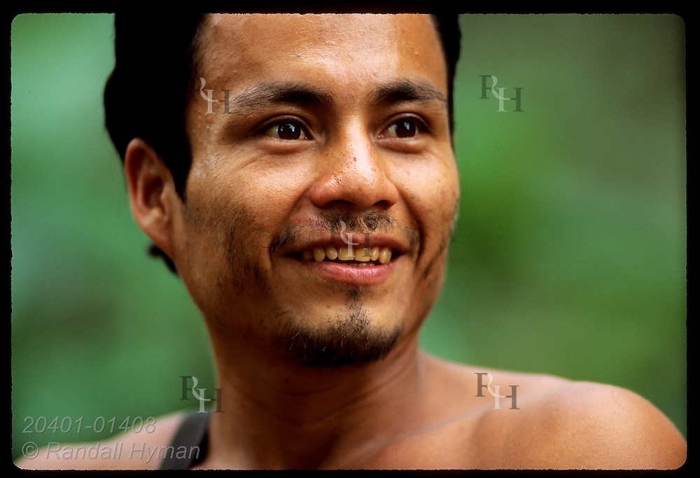 Young man beams with eager energy of a new colonist in vanishing rain forest of Fila de Mono. Ecuador