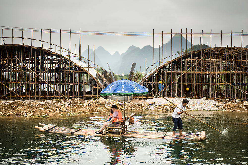Tourists on a bamboo raft float in front of construction workers building a bridge on the Li River near Yangshuo, China.