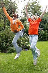 Portrait of two teenage girls jumping,