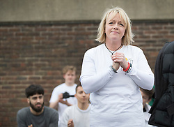 © Licensed to London News Pictures. 04/03/2017. Guildford, UK. Deborah Newman clasps her hands during a minutes silence at a memorial with hundreds of free runners gathered to remember her son Nye Newman who died in January. Nye Newman, whose death is thought not to be related to Parkour, died in Paris. Free running or Parkour involves jumping and climbing on building, railings and walls.  Photo credit: Peter Macdiarmid/LNP