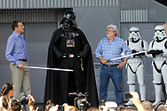 Darth Vader, center, play-acts with The Walt Disney Company CEO Robert Iger, left, and Star Wars creator George Lucas, third from right, during the re-opening celebration of the Star Tours motion simulation ride at the Disney Hollywood Studios theme park in Lake Buena Vista, Fla., Friday, May 20, 2011. (AP Photo/Phelan M. Ebenhack)