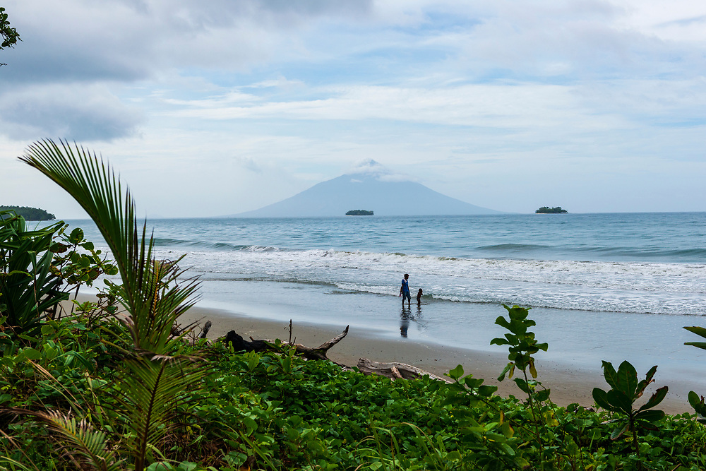 A woman and child walk at a beach on the north coast of Papua New Guinea, not far from Bogia. In the distance in Manam Island, an active volcano.<br /><br />(July 25, 2017)