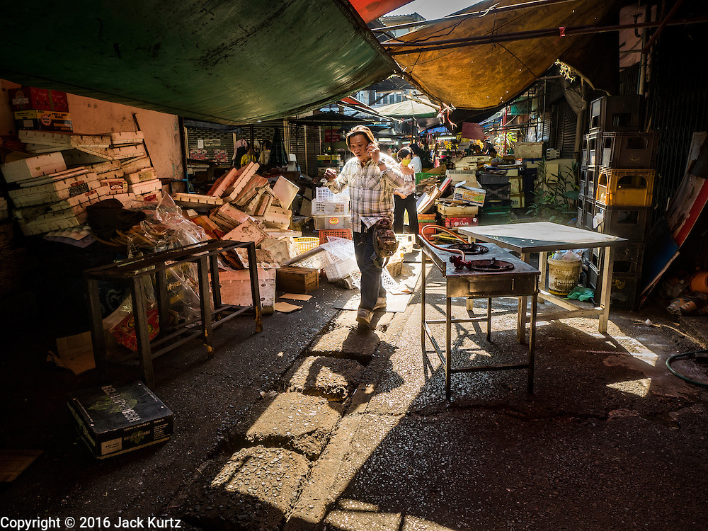 04 JANUARY 2016 - BANGKOK, THAILAND:        A person walks past trash from closed shops in Bang Chak Market on the last day the market was open. The market closed January 4, 2016. The Bang Chak Market serves the community around Sois 91-97 on Sukhumvit Road in the Bangkok suburbs. About half of the market has been torn down. Bangkok city authorities put up notices in late November that the market would be closed by January 1, 2016 and redevelopment would start shortly after that. Market vendors said condominiums are being built on the land. PHOTO BY JACK KURTZ