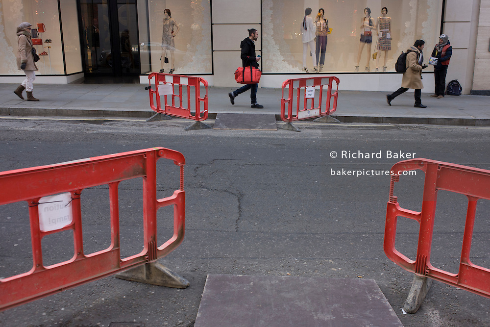 Four barriers positioned to help disabled public negotiate kerbs in Bond Street.