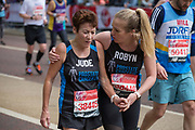 A young women supports an older female teammate on Birdcage Walk during The Virgin London Marathon on 28th April 2019 in London in the United Kingdom. Now in it's 39th year, the London Marathon is a large sporting event with over 40,000 runners expected to take part.