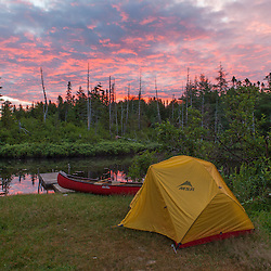 """Tent and canoe next to the Cold Stream """"deadwater"""" above Upper Cold Stream Falls in Maine's Northern Forest. Sunrise. Johnson Mountain Township."""