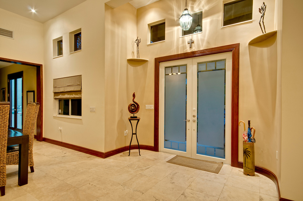 View of a modern home halway and entrance with glass door.