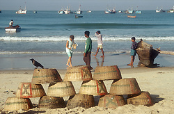Beach scene in Goa; India; with fishing baskets piled up in the foreground,