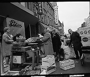 Moore Street, Dublin.      (J97)..1975..23.12.1975..12.23.1975..23rd December 1975..For well over a hundred years Moore Street has served the citizens of Dublin. The longest running open air fruit and vegatable market offers value for money,particularly to those where money is in short supply. Predominately a fruit and veg market there are several traders who sell fish and seasonal goods, as illustrated by the photographs showing turkeys and holly wreaths being sold on the run up to Christmas..Image shows the stall holders most important piece of equipment, The Scales, note the weights beside it. the weights were in ounces and pounds.