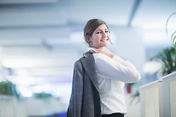 Businesswoman carrying suit on her shoulder and smiling in office, Freiburg Im Breisgau, Baden-Württemberg, Germany