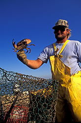 Stock photo of a man on a boat holding up a freshly caught crab