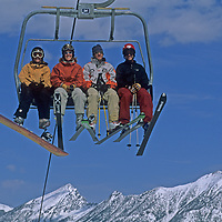 Skiers ride the Ram Charger high-speed quad lift on Andesite Mountain at Montana's Big Sky Resort.