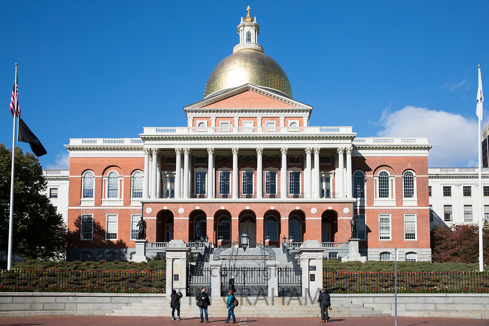 Tourists at Massachusetts State House seat of Government, with golden dome and patriotic Stars and Strips flag in Boston, USA