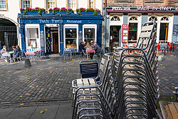 Edinburgh, Scotland, UK. Members of the public sitting outdoors at a cafe and restaurant in Grassmarket in Edinburgh. The Scottish Government covid regulations beginning at 6pm today means cafes, bars and licensed restaurants in Lothian and the central belt of Scotland  must close for 16 days. Iain Masterton/Alamy Live News