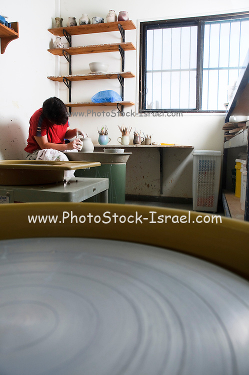 An European female potter in her workshop works on a potter's wheel