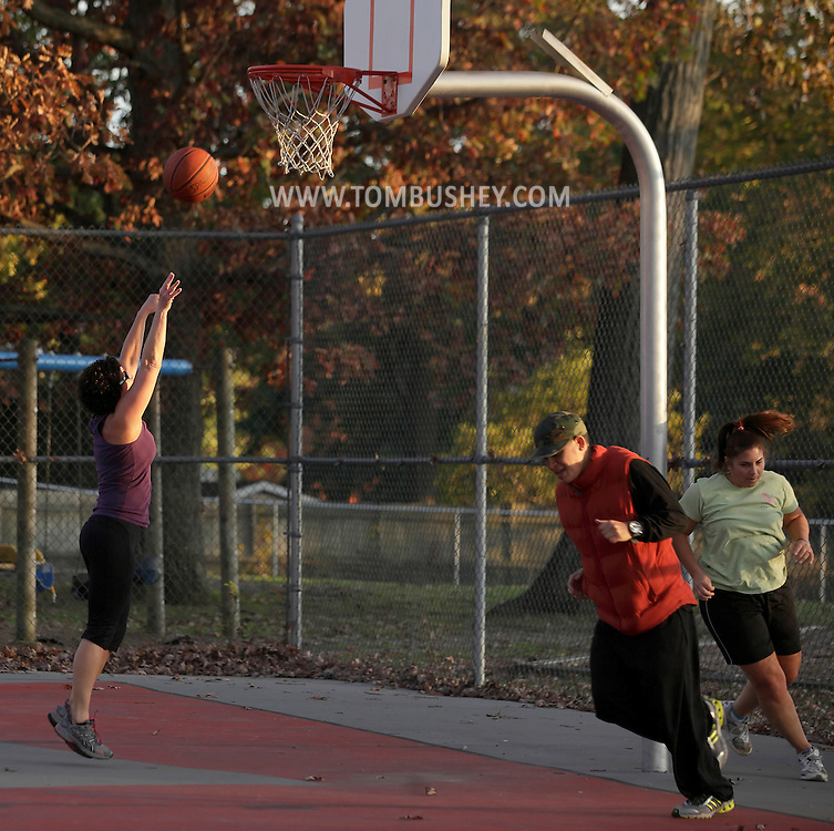 Middletown, New York  -Three women exercise on a park basketball court during a Boot Camp class on Oct. 23, 2011.