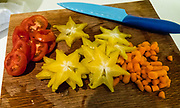Sliced starfruit, tomatoes and carrots on a cutting board. Starfruit (Averrhoa carambola) is a tree native to the Philippines, Indonesia, Malaysia, Vietnam, Nepal, India, Bangladesh, Sri Lanka, Mauritius and Seychelles. The popular fruit is widey cultivated in tropical areas, such as in Latin America, the Caribbean, Africa, and southern United States.