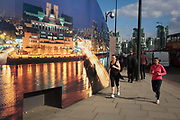 "Lady joggers run past CCTV a camera and a construction hoarding, a night time panorama of the Thames south bank, featuring the HQ of the intelligence service (MI6) across the river in Vauxhall. Under the gaze of a CCTV camera, the two women pass the temporary hoarding which will stay in place for the time that the company's new residential riverfront apartments are under construction. In the image, the building at Vauxhall Cross, is located at 85 Albert Embankment beside Vauxhall Bridge. It is known within the intelligence community as ""Legoland"" and ""Babylon-on-Thames""."
