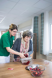 Nurse preparing dessert with senior woman in rest home