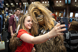 © Licensed to London News Pictures . 26/07/2015 . Manchester , UK . A woman poses for a selfie with Chewbacce , inside the venue . Comic Con convention at Manchester Central Convention Centre . Photo credit : Joel Goodman/LNP