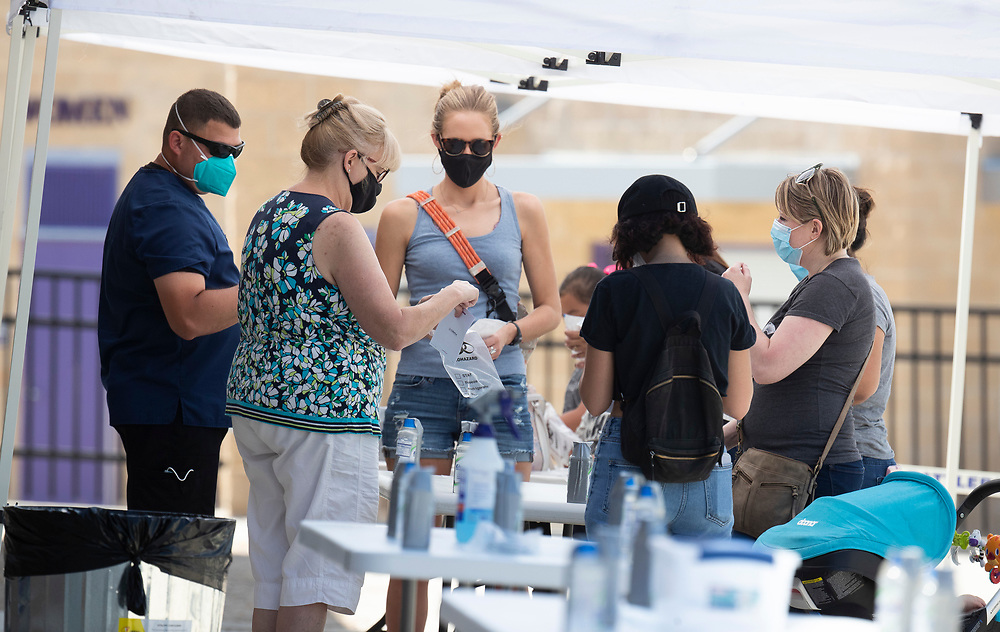 San Marcos, TX USA July 14, 2020: Central Texas residents complete a non-contact COVID-19 self-test during a free clinic sponsored by the Texas Dept. of Health. Texas has seen a huge spike in cases after an early reopening last month with a total of over 3,200 deaths attributed to the virus.