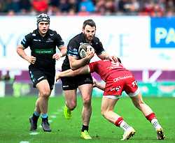 Glasgow Warriors' Tommy Seymour is tackled by Scarlets' Gareth Davies<br /> <br /> Photographer Simon King/Replay Images<br /> <br /> Guinness PRO14 Round 19 - Scarlets v Glasgow Warriors - Saturday 7th April 2018 - Parc Y Scarlets - Llanelli<br /> <br /> World Copyright © Replay Images . All rights reserved. info@replayimages.co.uk - http://replayimages.co.uk