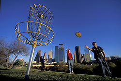 Stock photo of three men playing frisbee golf on a course in Memorial Park just outside of downtown Houston Texas