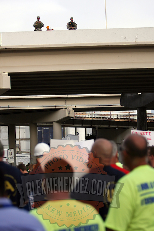 Police officers observe from an overhead highway bridge as protesters carry signs while marching in a parade during the Republican National Convention in Tampa, Fla. on Wednesday, August 29, 2012. (AP Photo/Alex Menendez)