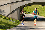 Jane and Arturs Bareikis operate in symmetry and become airborn in unison as they take the incline out of the tunnel at the 8th mile mark of the Soldier Field 10 Mile race on Memorial Day Weekend.