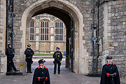 The day after the death at age 99 of Prince Phillip, the Duke of Edinburgh, consort to Queen Elizabeth II, armed police officers and a woman member of the Royal Household stand outside Windsor Castle where the Queen has been isolating throughout the Coronavirus pandemic, on 10th April 2021, in London, England.