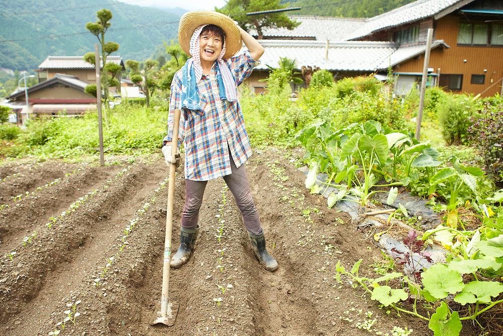 Lifestyle image of laughing woman in her 60s farming in Japanese countryside