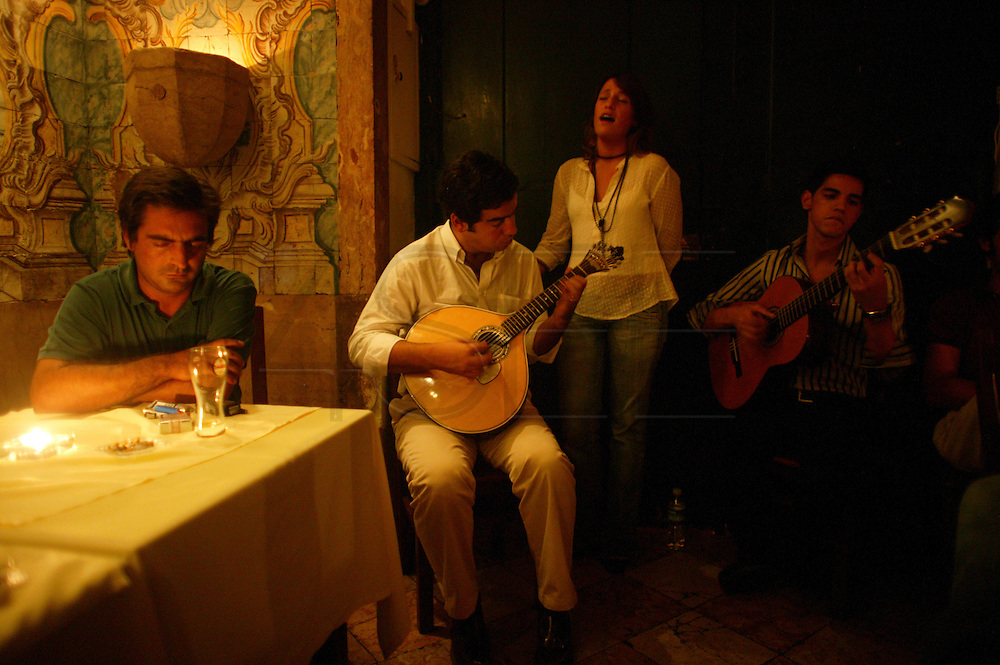"""Singer Carminho performing at restaurant """"Mesa de Frades"""", an old chapel in Alfama typical neighborhood. On the left side the acclaimed singer Camane listens her singing."""