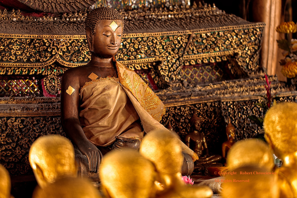 The Dao: Statues depict the Lord Buddha teaching the Dao, the way or path, to his golden disciples at the base of the temple in Wat Thepthidaram Worawihan, Bangkok Thailand.