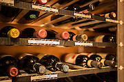 New York, NY, Sept. 30, 2013. Grant Reynolds, wine director at Charlie Bird. Racks in the dining room wine storage.