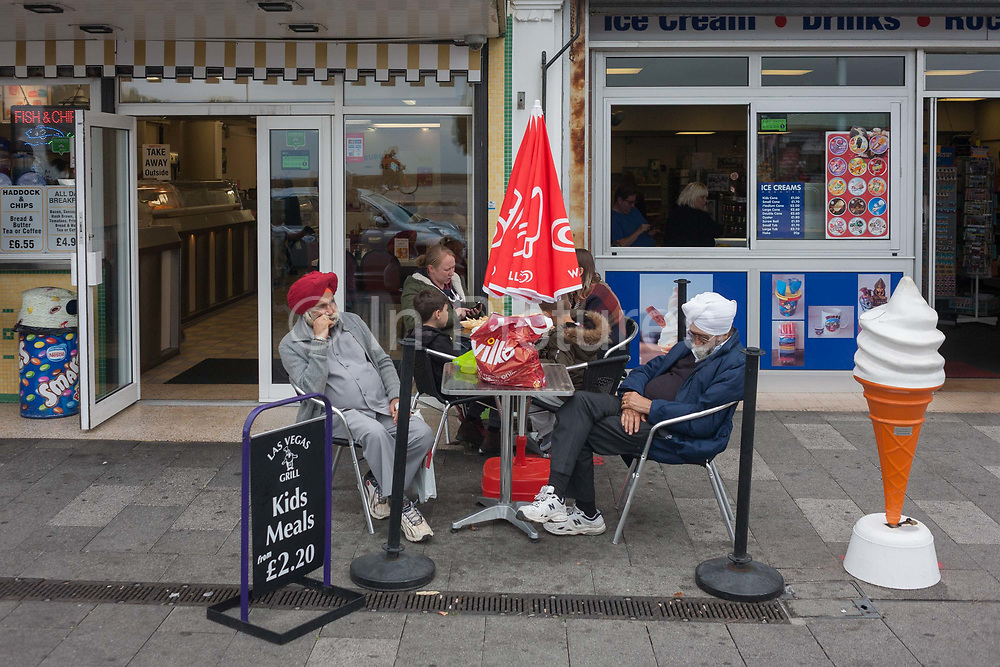 Tired sikh gentlemen rest outside an ice cream parlour on 17th September 2016, on the Eastern Esplanade, at Southend, Essex, England. One sleeps and the other is in distant thought on the pavement outside. Southend-on-Sea is a seaside town on the north side of the Thames estuary 40 miles 64 km east of central London. In its heyday, the working class visited from the capital when train transport allowed them to enjoy its beaches and the worlds longest pier. Its splendour faded on the advent of package holidays to Spain etc.