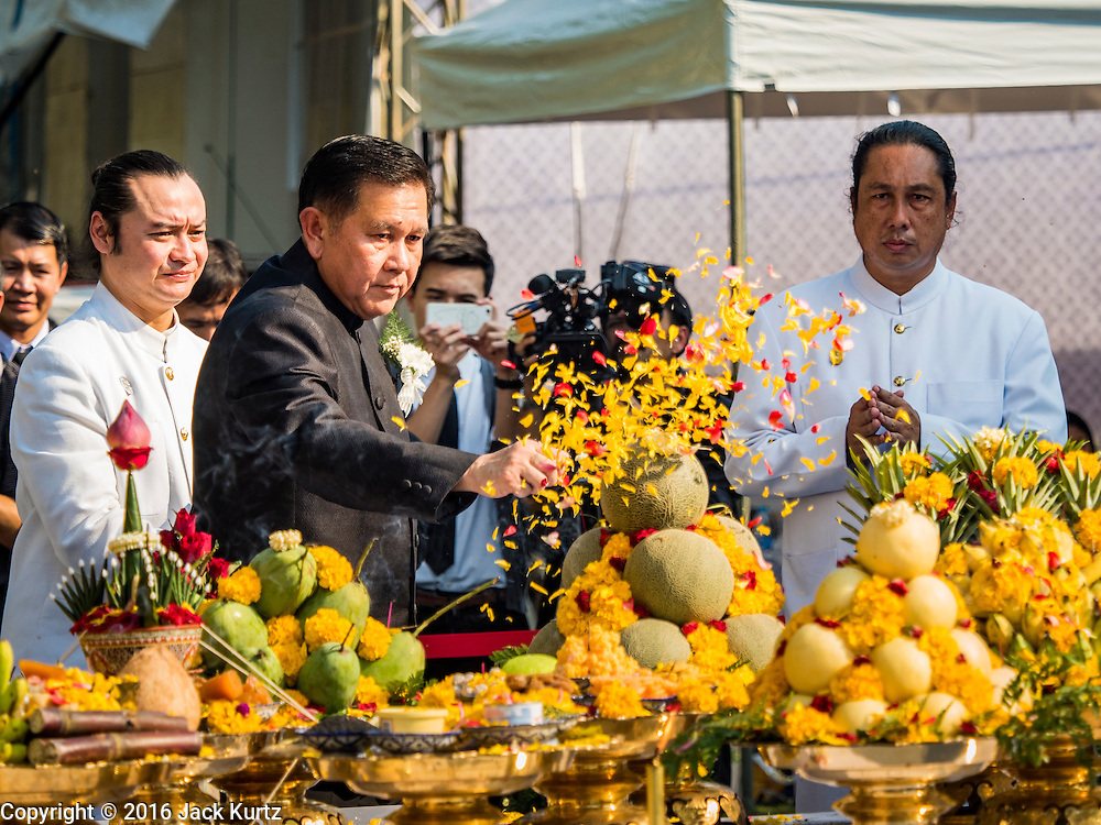 """19 DECEMBER 2016 - BANGKOK, THAILAND: A Thai government official spreads marigold petals on the offerings for the """"Spirit Appeasing"""" Ceremony held for the Royal Chariots at the Bangkok National Museum. The chariots will be used to take the body of Bhumibol Adulyadej, the Late King of Thailand, and members of the Royal funeral cortege to the cremation site on Sanam Luang for His Majesty's cremation. This will be the first cremation of a Thai King since 1950, when King Bumibol's brother, Rama VIII, Ananda Mahidol, was cremated. The design of the royal crematorium is based on Buddhist cosmology, with the main peak of Mount Sumeru (also known as Meru in Hindu cosmology) at center and eight other peaks signifying the levels of the universe. The crematorium will be decorated with mythical creatures such as garuda, angels, and Himmapan Forest creatures. The structure and funeral pyre will stand just over 50 meters tall. The exact date of the King's cremation has not been set yet but is expected to be late next year.     PHOTO BY JACK KURTZ"""